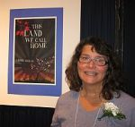 Alison Lohans with the poster of her book This Land We Call Home